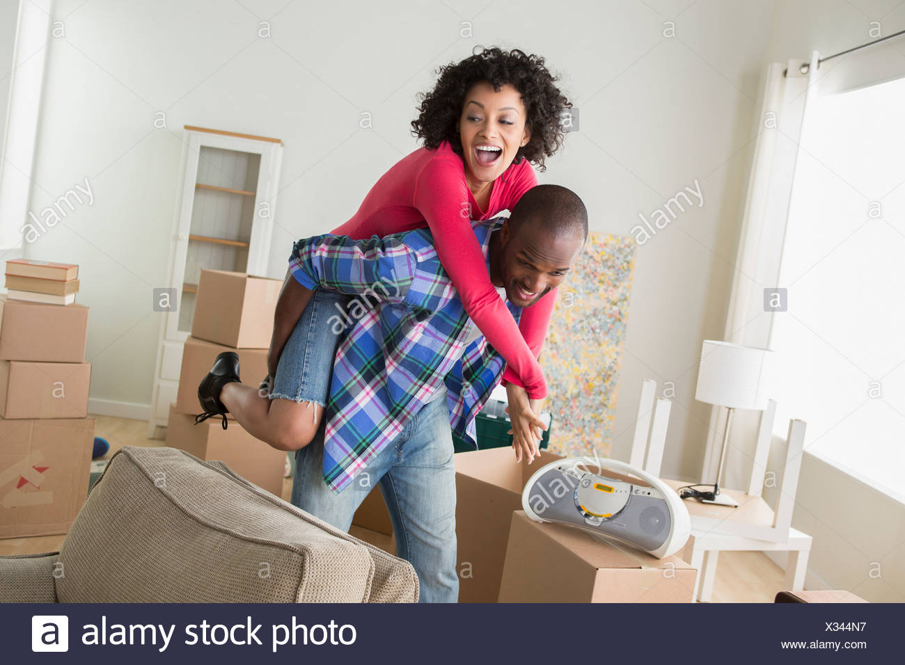 Mid adult couple in new home, man giving woman piggyback - Stock Image