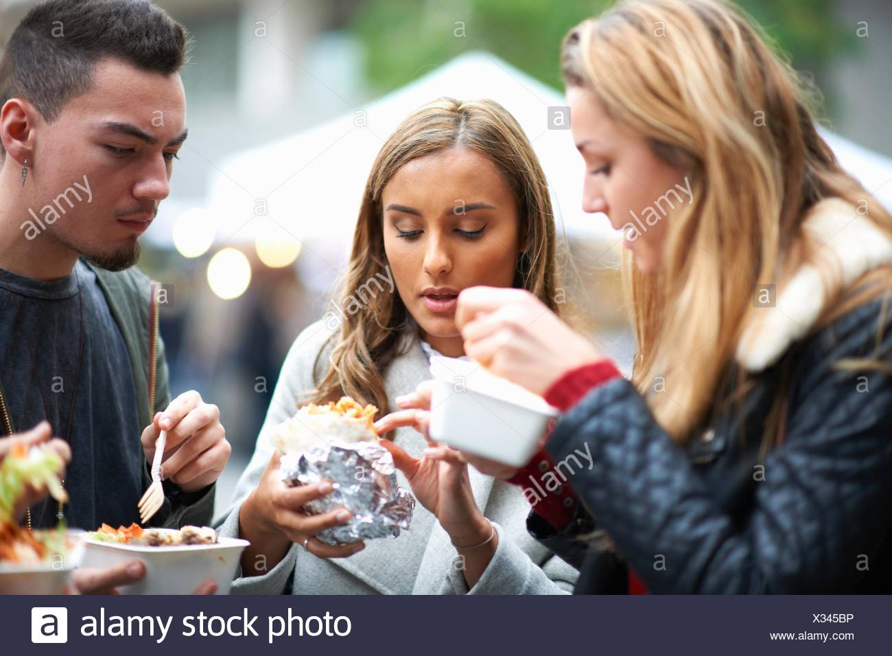 Group of young adults eating takeaway food, outdoors Stock Photo