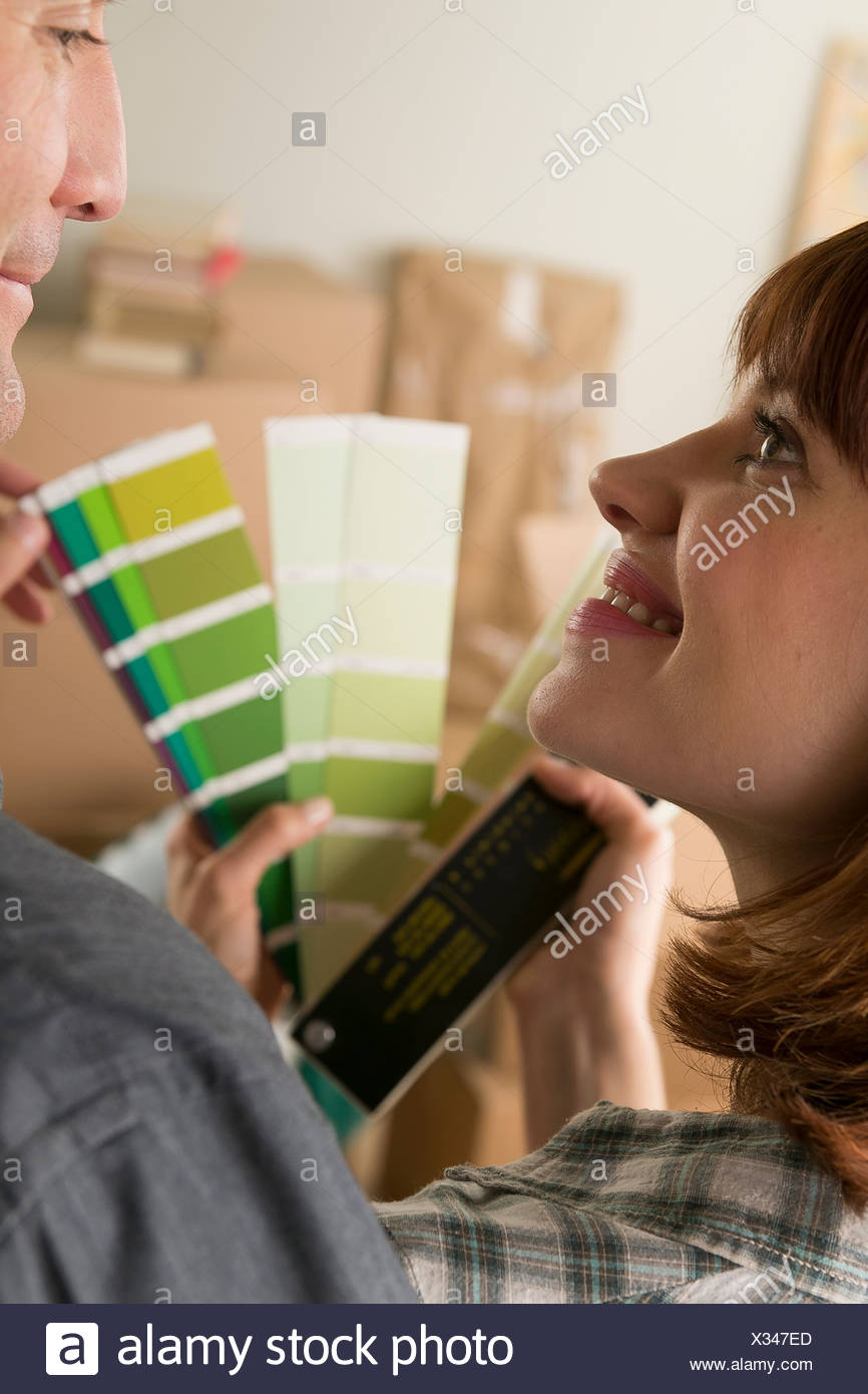 Couple looking at green swatch in new home - Stock Image