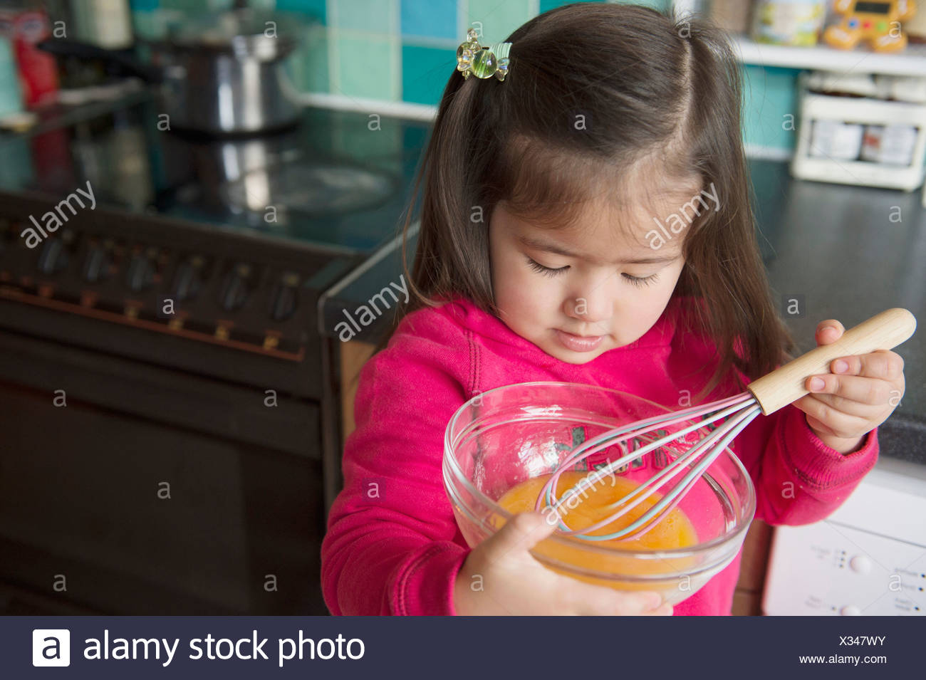 Girl learning to cook - Stock Image