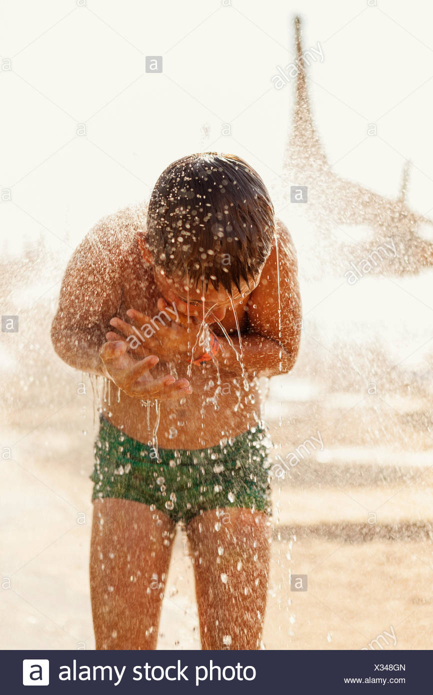 Turkey, Alanya, Boy (10-11) under shower on beach - Stock Image