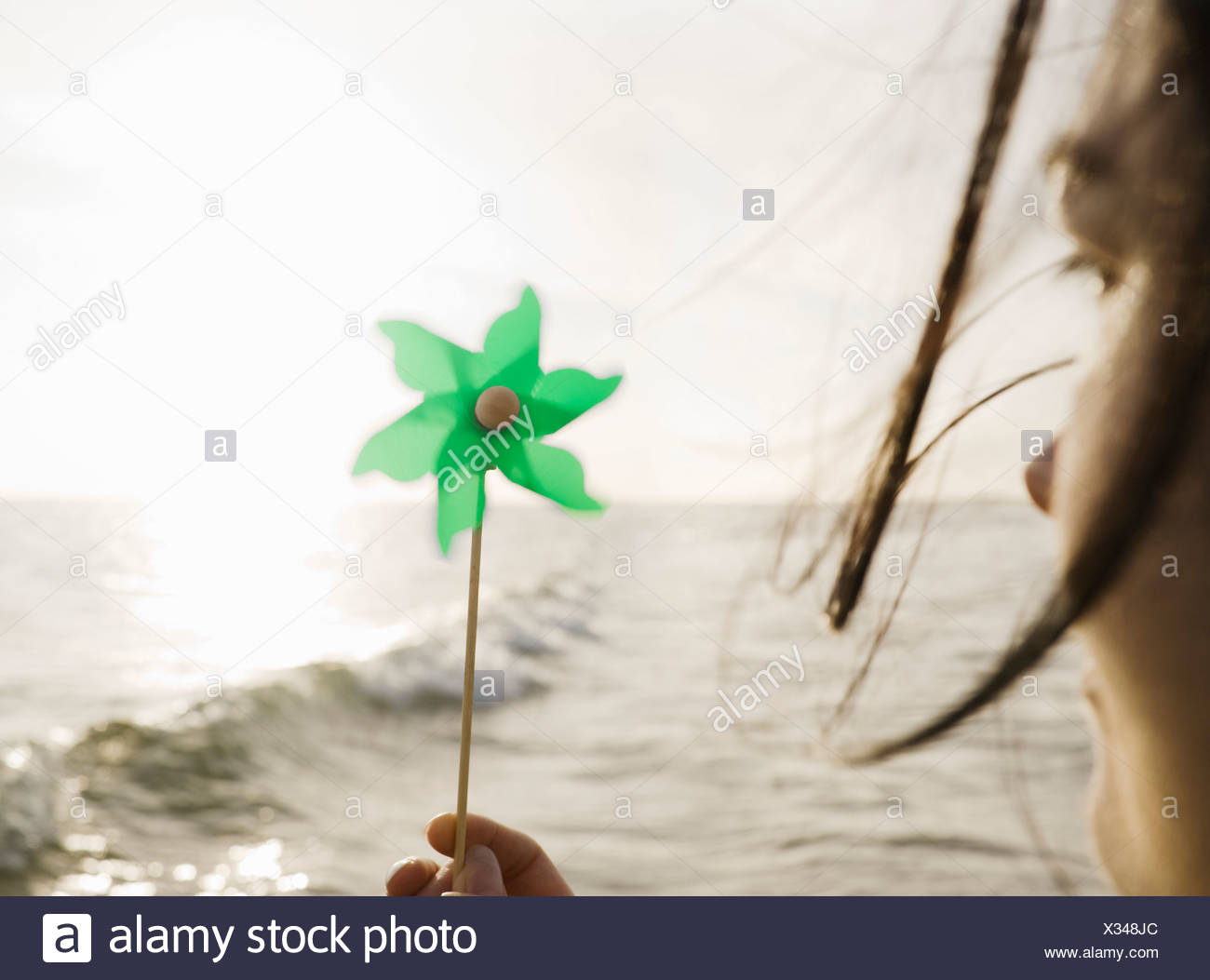 Woman holding windmill towards sea - Stock Image