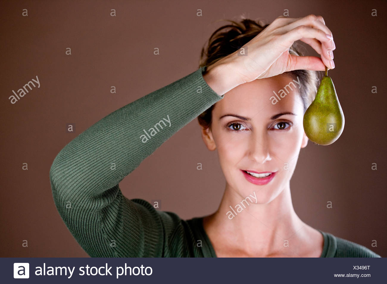 A mid adult woman holding a pear - Stock Image