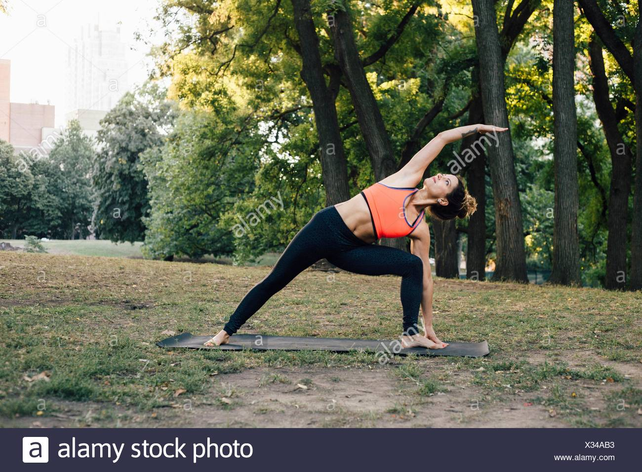 Woman in Extended Side Angle pose (Utthita Parsvakonasana) - Stock Image