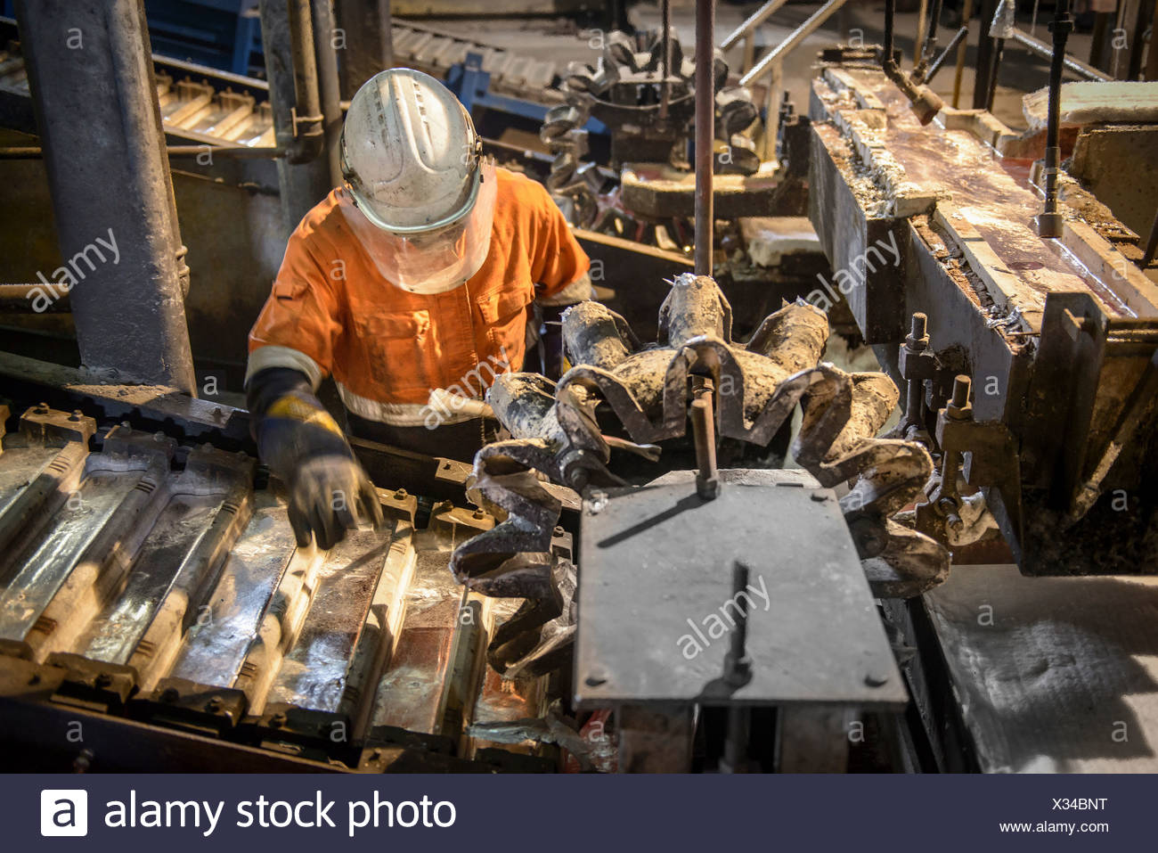 Worker testing metal ingots at aluminum recycling plant - Stock Image