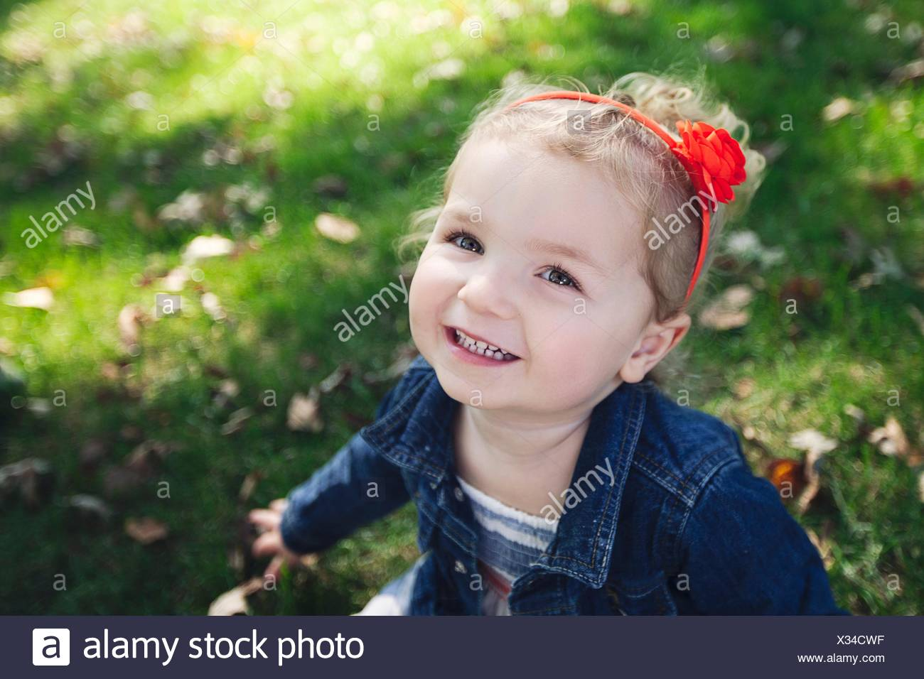 High angle portrait of girl with red hairband wearing denim jacket looking at camera smiling - Stock Image