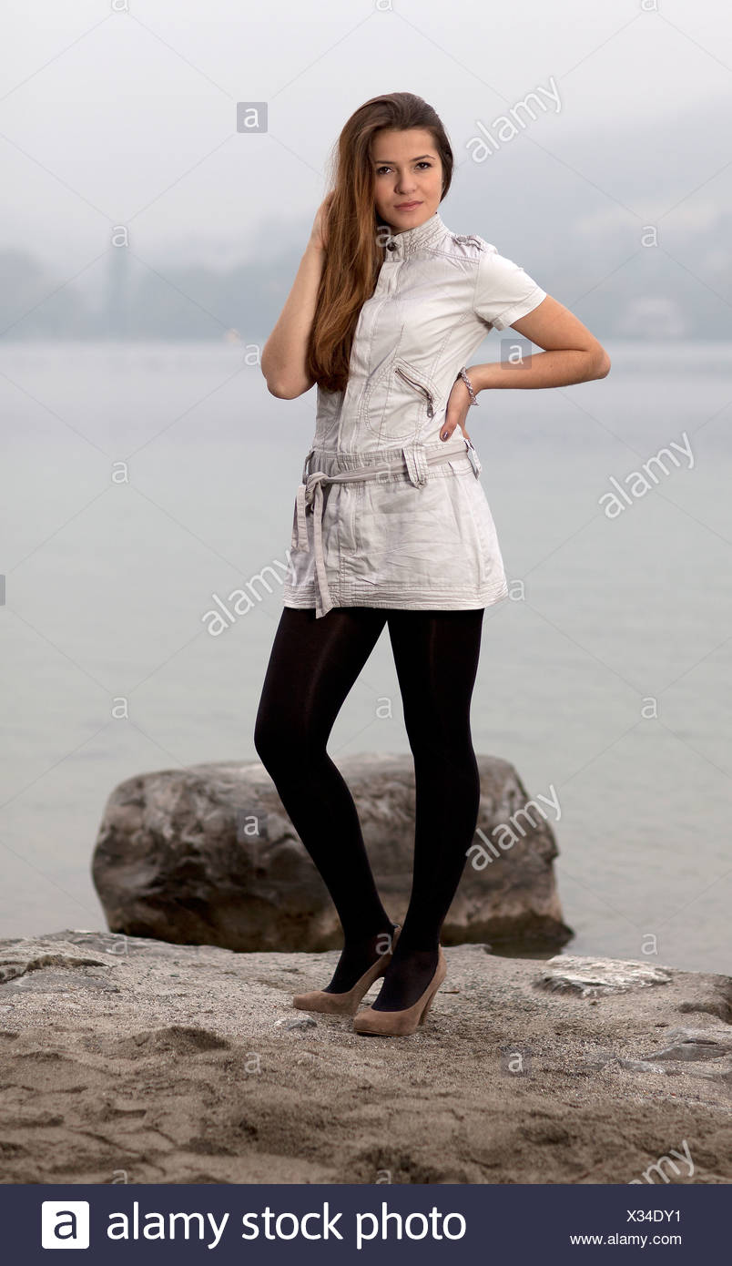 Young woman posing on the seashore - Stock Image