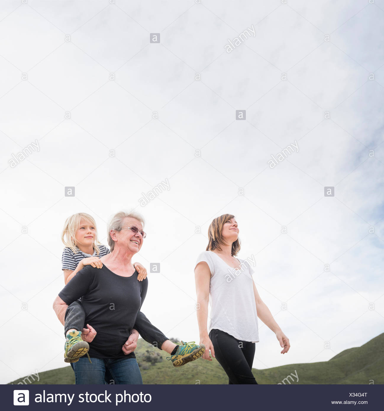 Senior woman walking with daughter and grandson - Stock Image