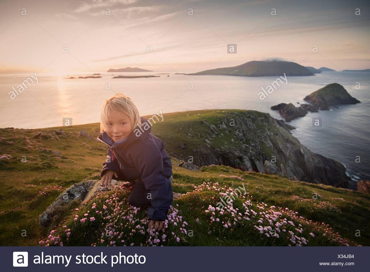 Young boy sitting on hillside, Slea head, County Kerry, Ireland - Stock Image