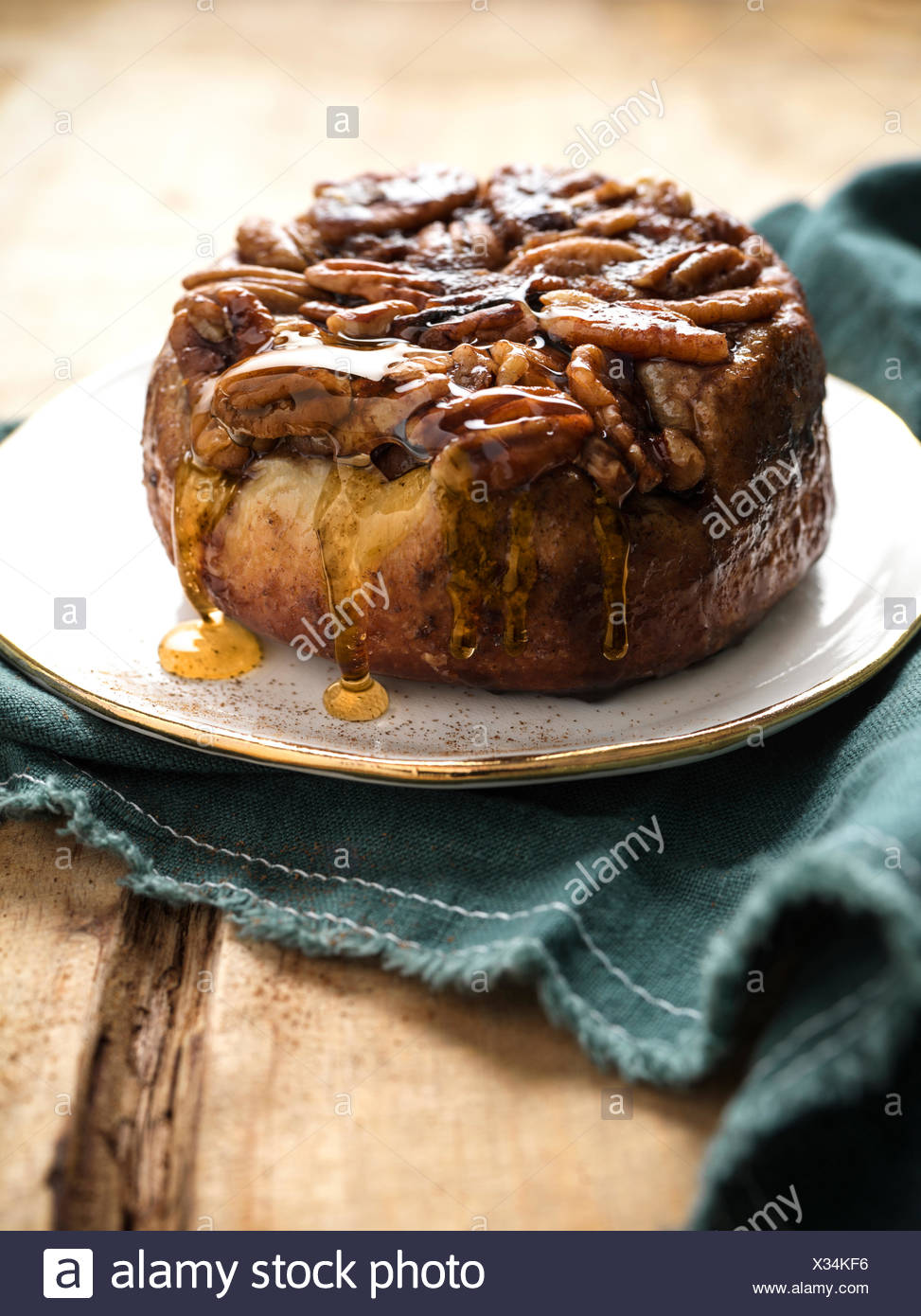 Beautiful, sticky pecan roll with honey glaze dripping off on a gold rim plate and rich green linen. - Stock Image