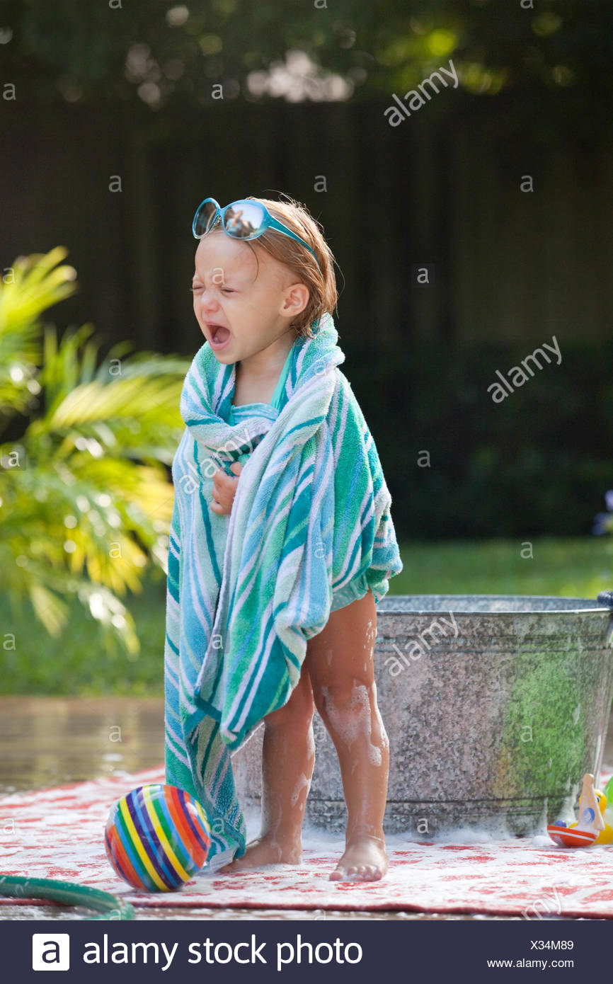 Female toddler wrapped in towel crying beside bubble bath in garden - Stock Image
