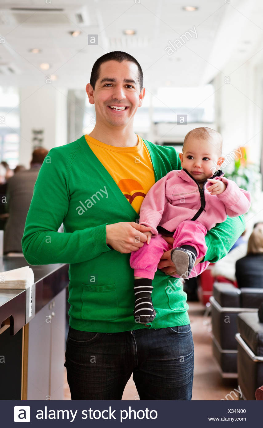 Happy father holding his daughter (0-11 months) - Stock Image