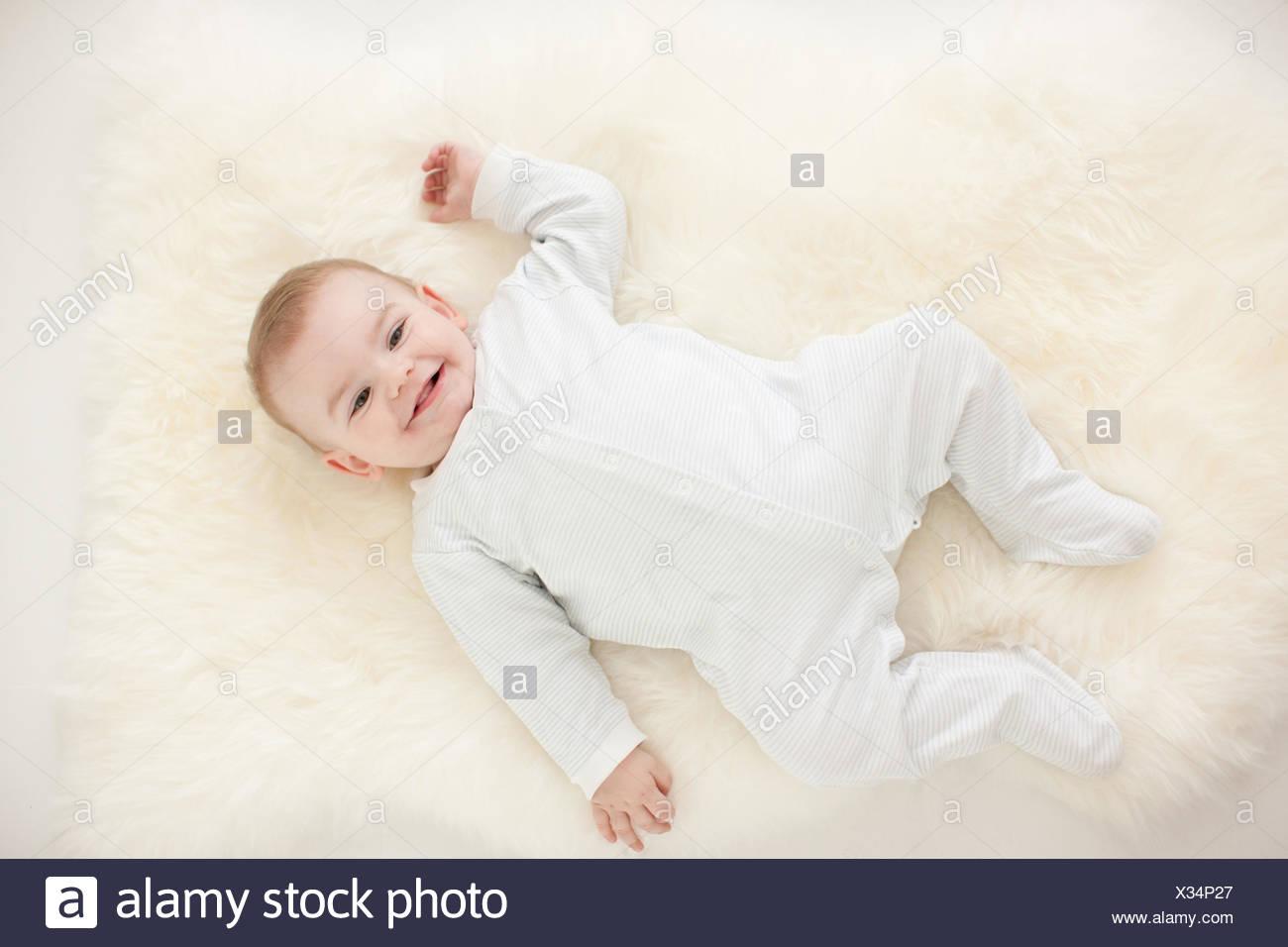 Smiling baby laying on rug - Stock Image
