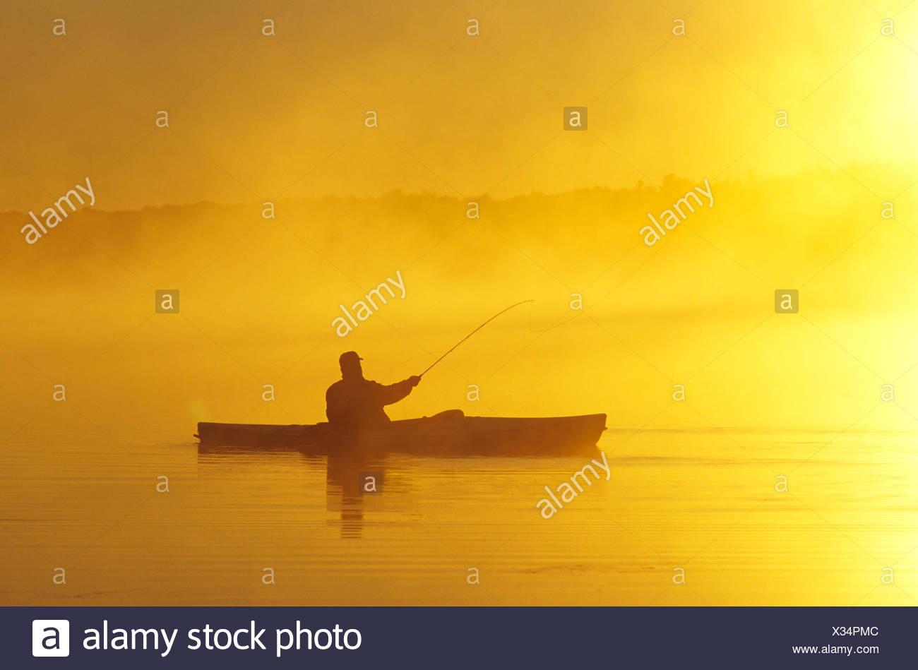 Middle-aged man fly fishing from sea kayak, Lake Muskoka, Ontario, Canada. - Stock Image