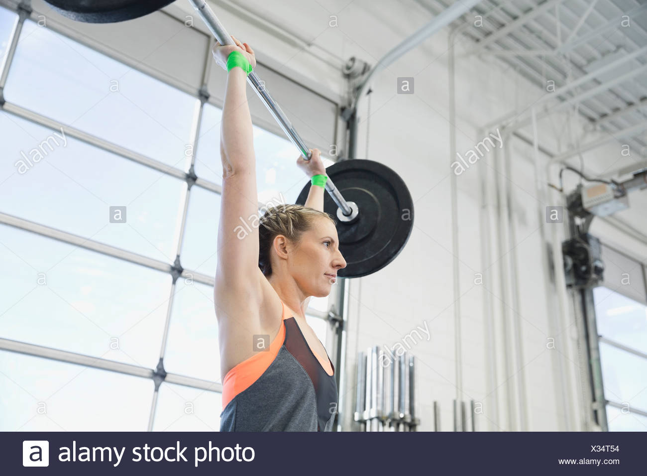 Woman practicing overhead lift with barbell - Stock Image