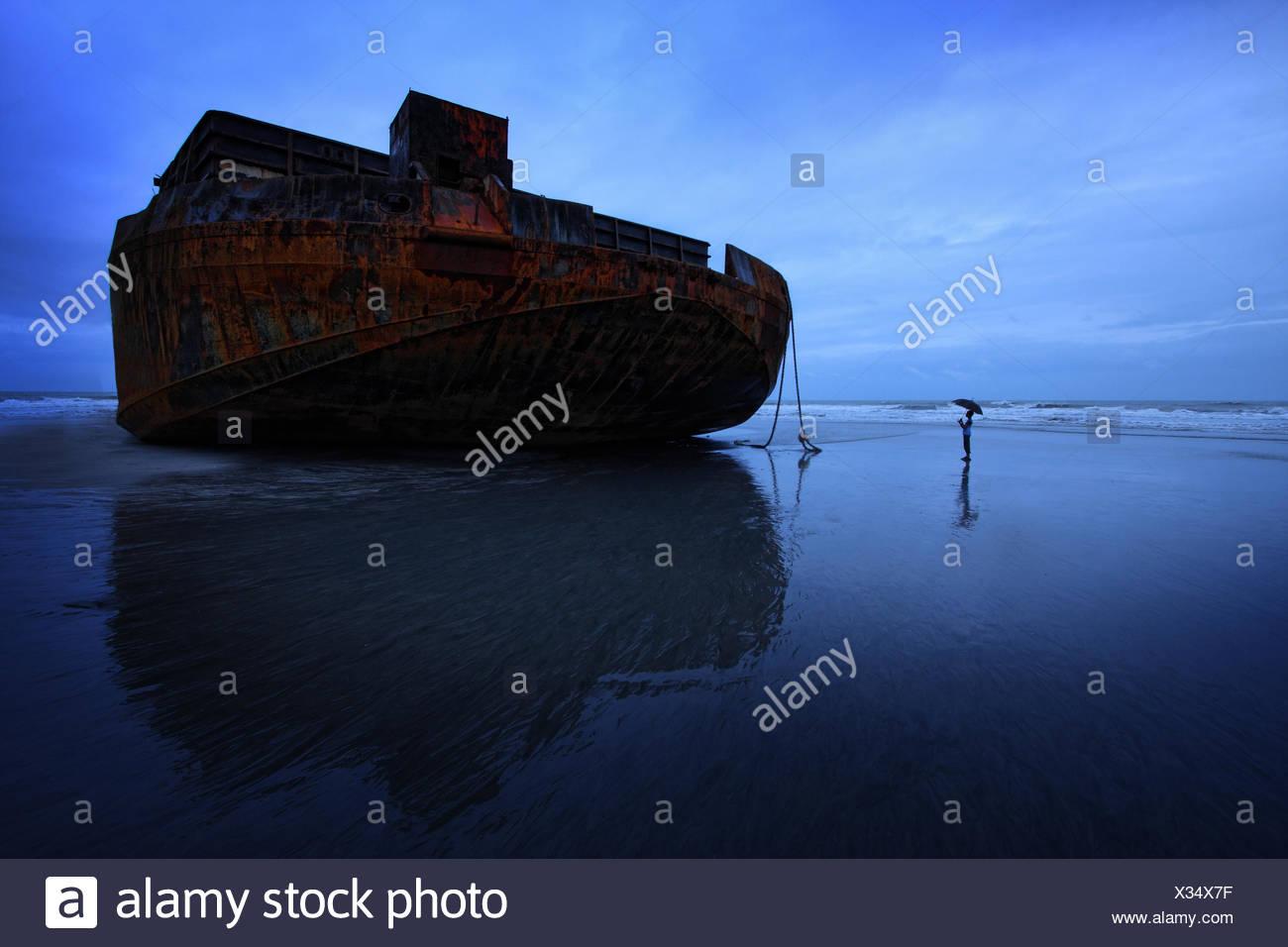 Boy (14-15) dwarfed by huge abandoned barge - Stock Image