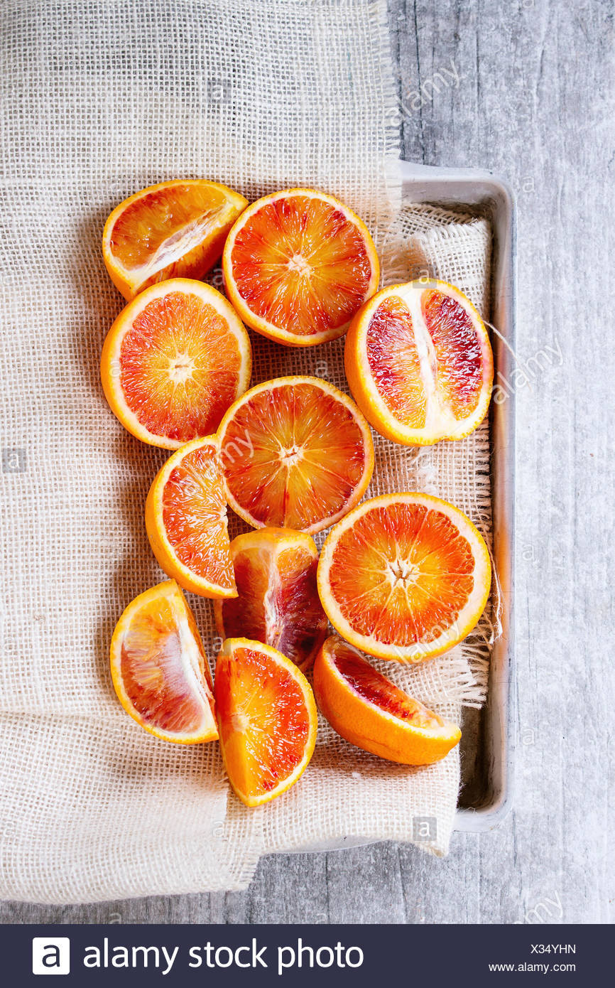 Sliced Sicilian Blood oranges fruits in aluminum tray with white sackcloth over gray wooden background. Top view - Stock Image