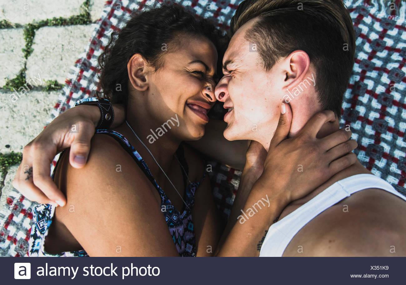 Intimate young couple lying on blanket - Stock Image
