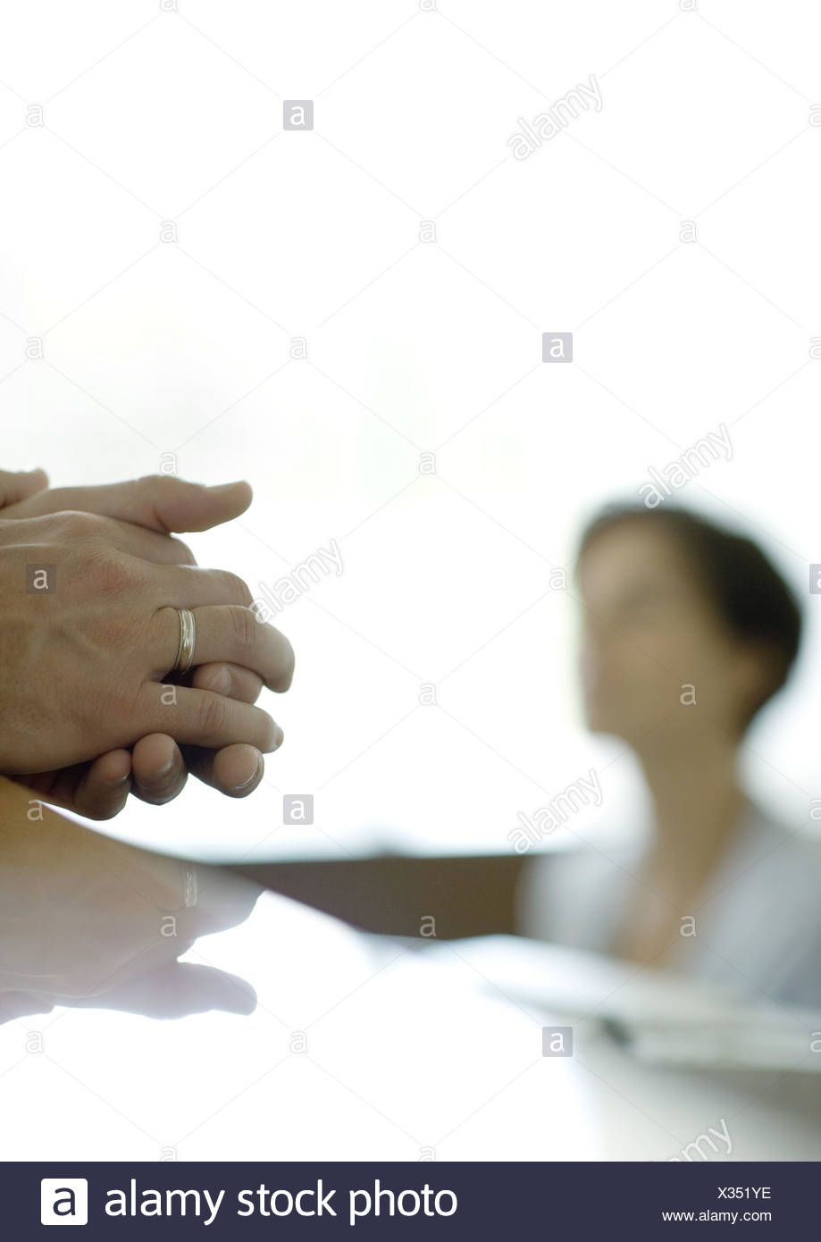 Man's clasped hands on reception desk, receptionist in background - Stock Image