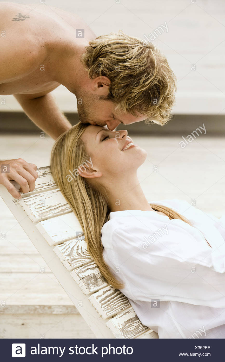 Man kissing tenderly a woman on her forehead - Stock Image