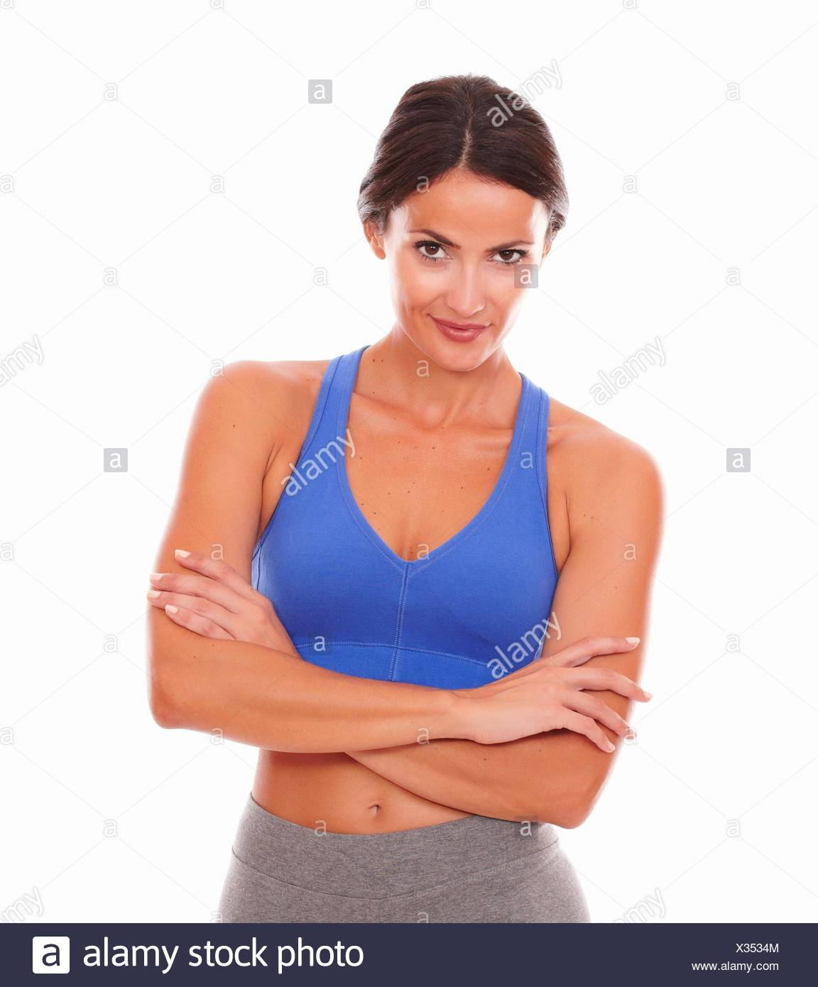 Latin lady in sports outfit looking at you against white background. Stock Photo