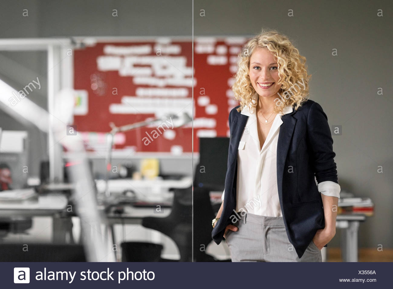 Dynamic businesswoman standing in office, smiling - Stock Image