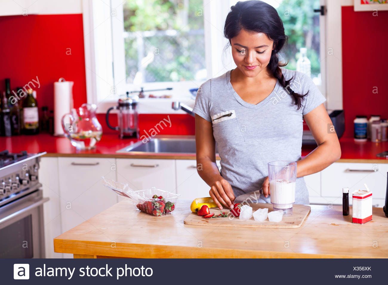 Young woman slicing strawberry in kitchen - Stock Image