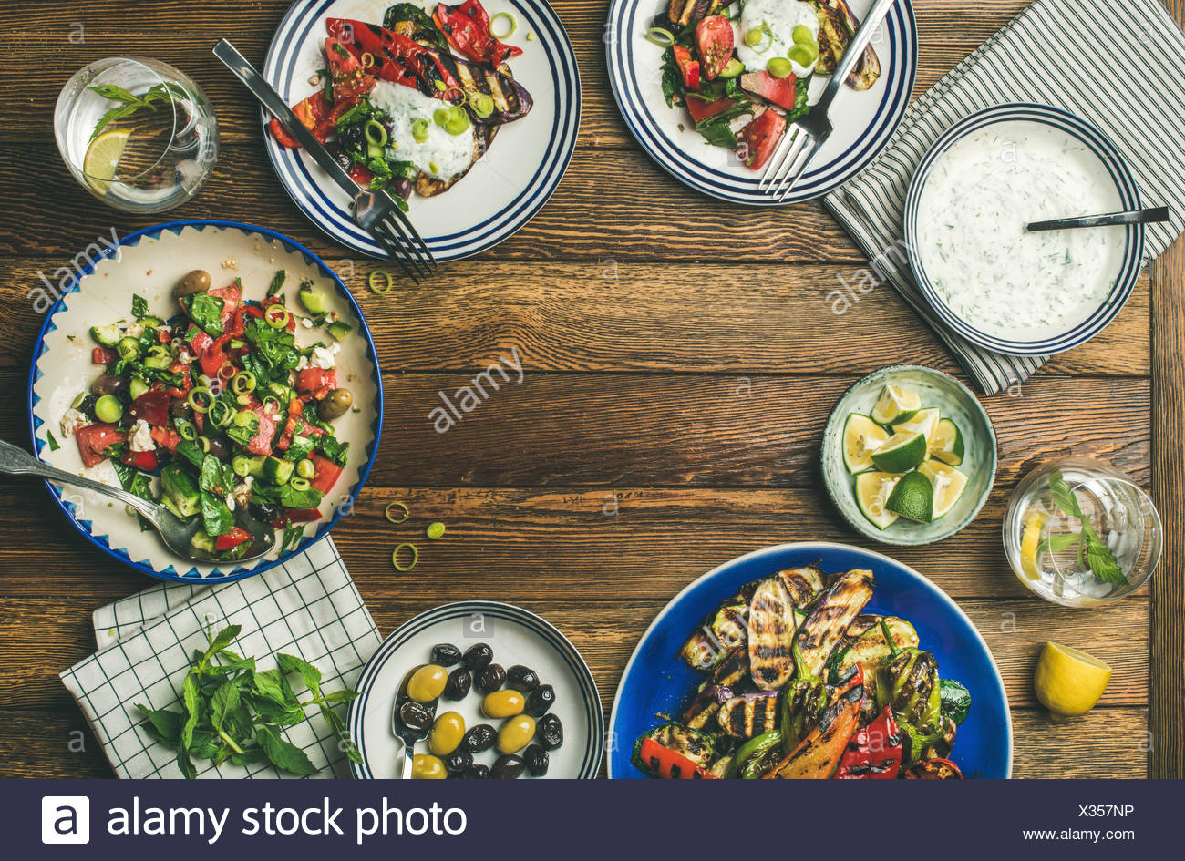 Flat-lay of healthy dinner table setting. Fresh salad, grilled vegetables with yogurt sauce, pickled olives over wooden background, copy space, select - Stock Image