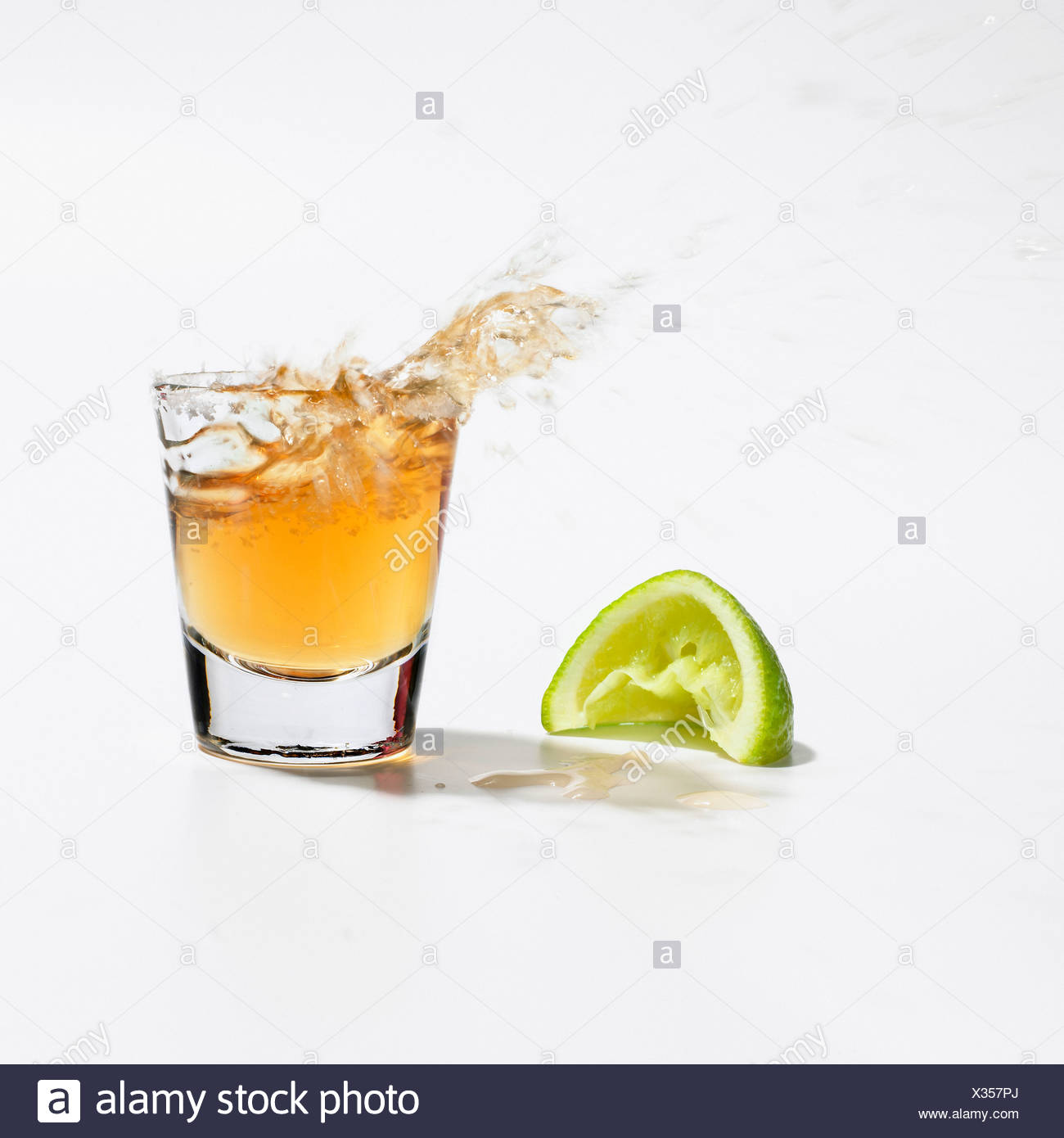 Close up of tequila splashing out of glass - Stock Image