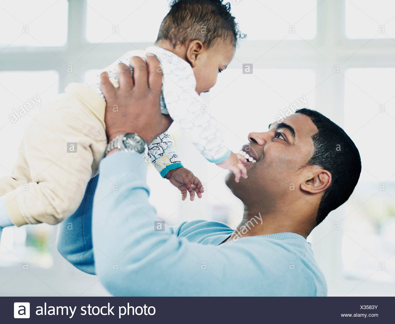 Father lifting baby boy - Stock Image