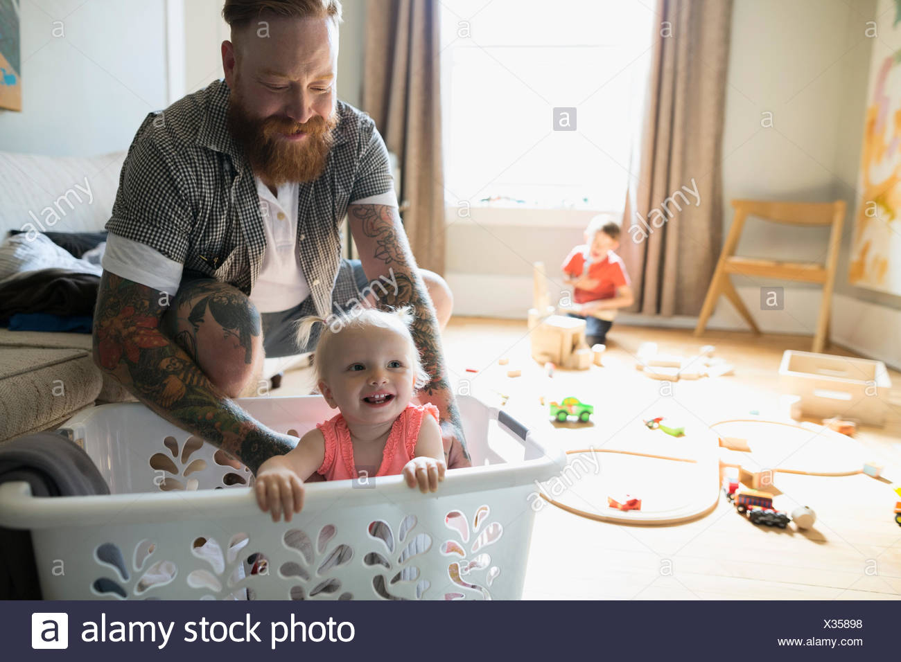 Father with happy daughter inside laundry basket - Stock Image