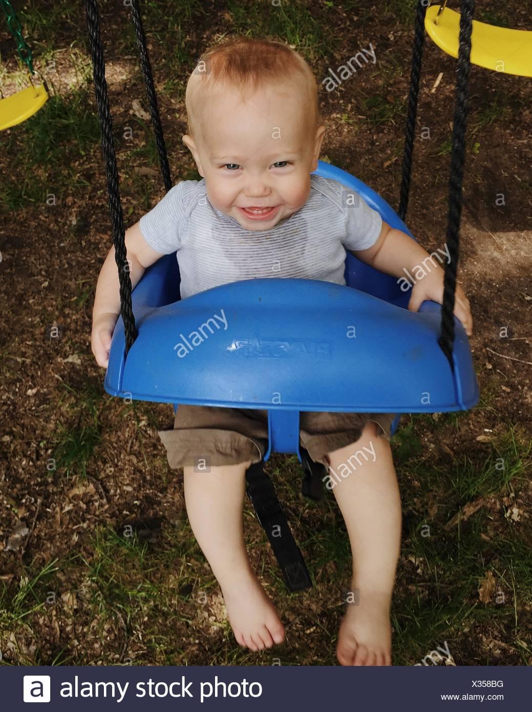 Portrait Of Happy Boy Swinging In Park - Stock Image