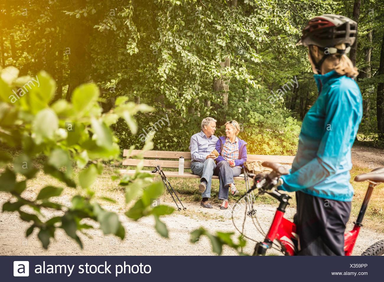Female mountain biker watching happy couple on park bench - Stock Image