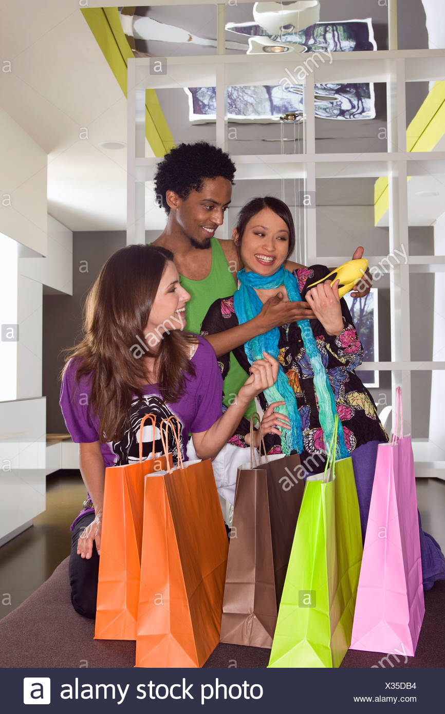 Young multi-ethnic friends shoe shopping - Stock Image