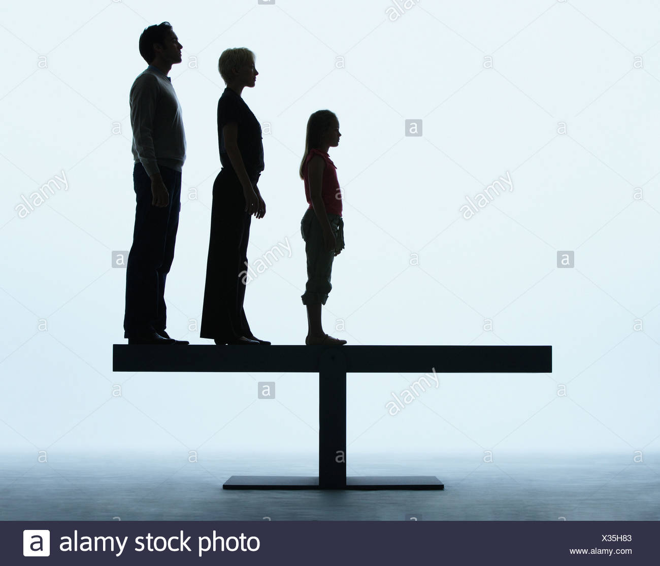 Couple and young girl standing in a line on a plank - Stock Image