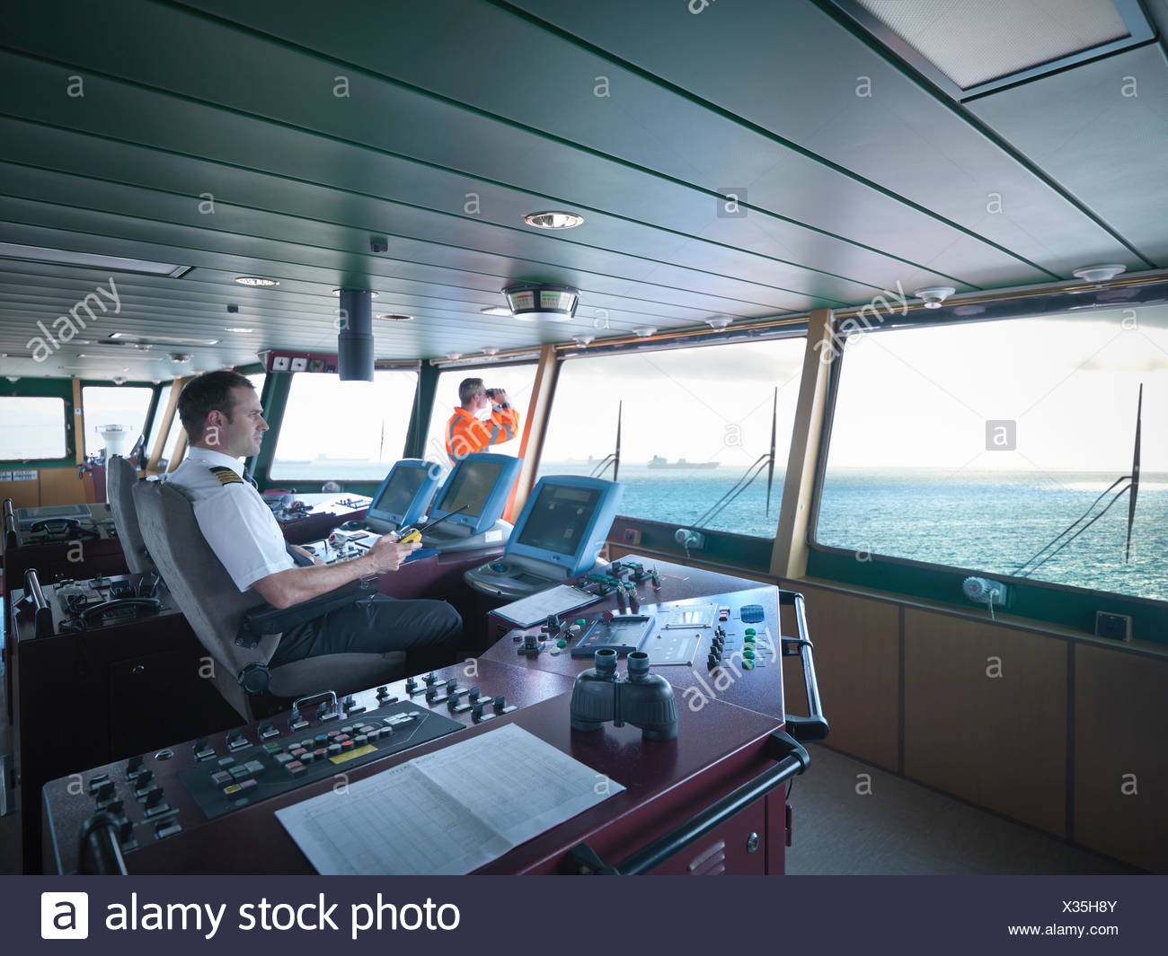 Captain and worker on bridge steering ship at sea - Stock Image