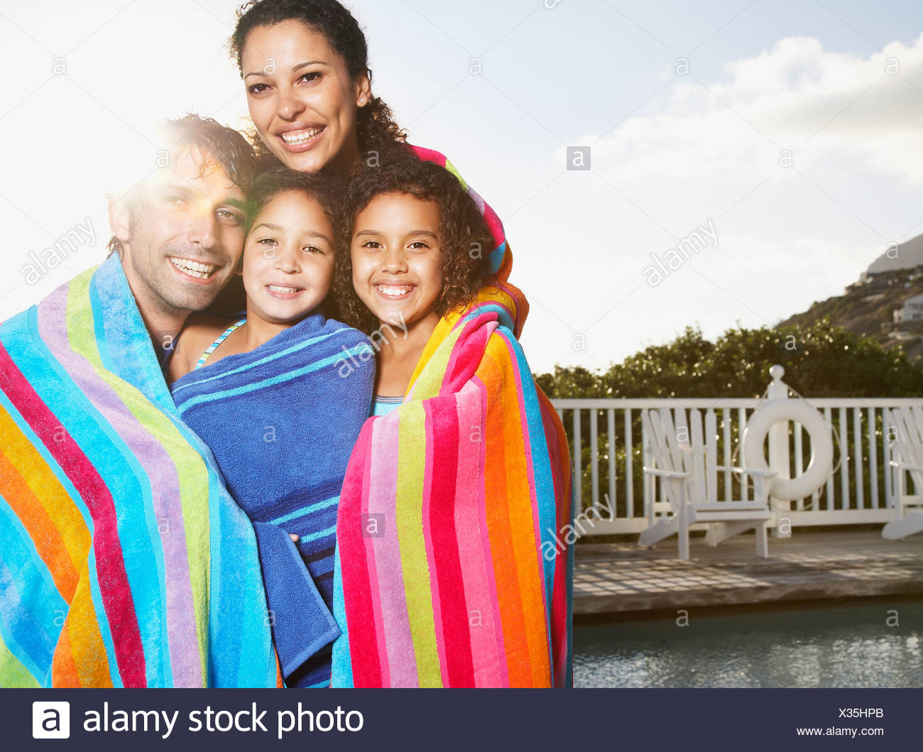 Man and woman with girls in beach towels by pool outdoors - Stock Image