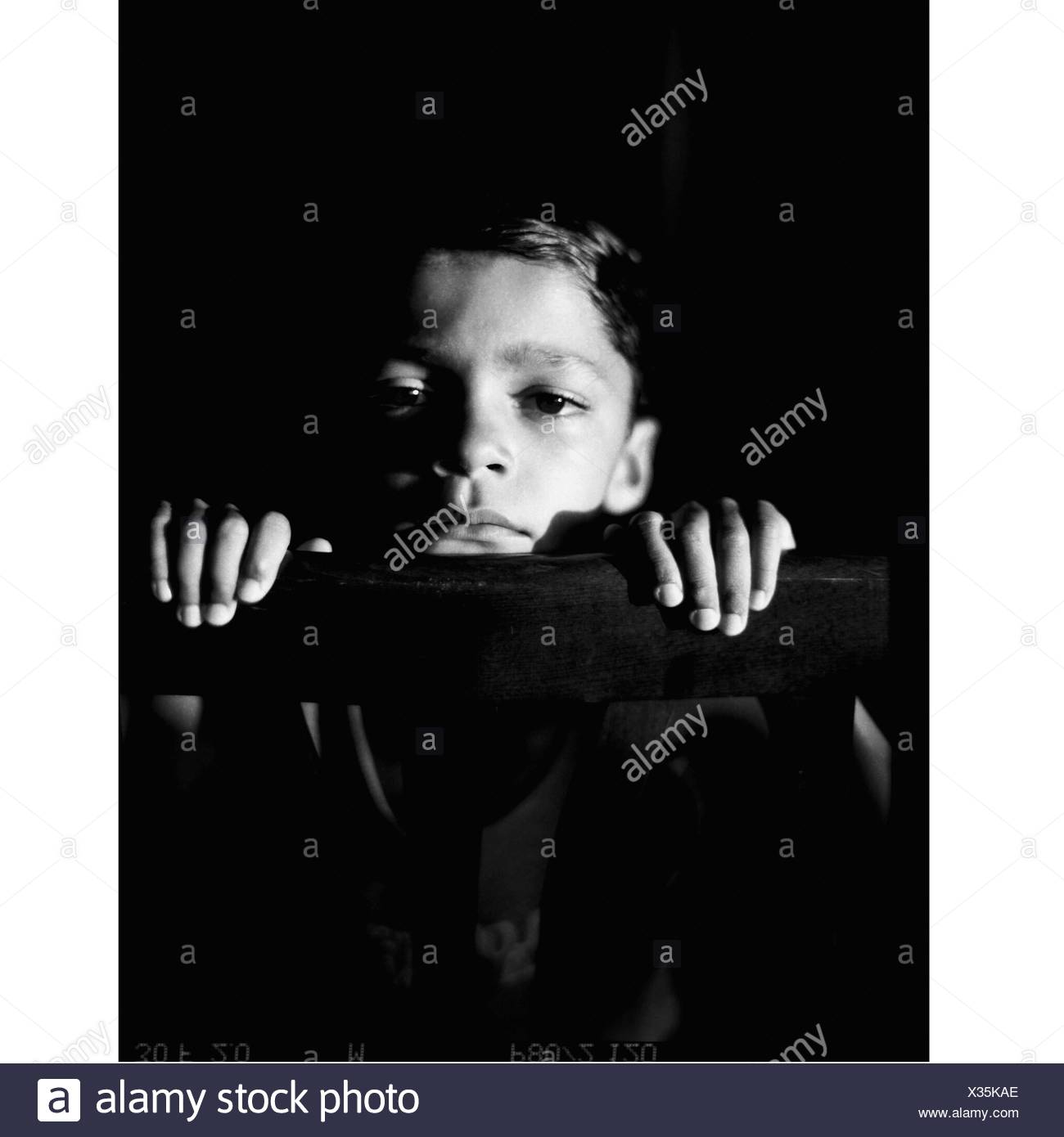 Portrait Of Boy Sitting By Railing - Stock Image