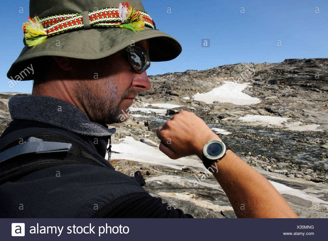 Man during an altitude check with a multifunction watch, hike, trekking in the Hundefjord, East Greenland, Greenland - Stock Image