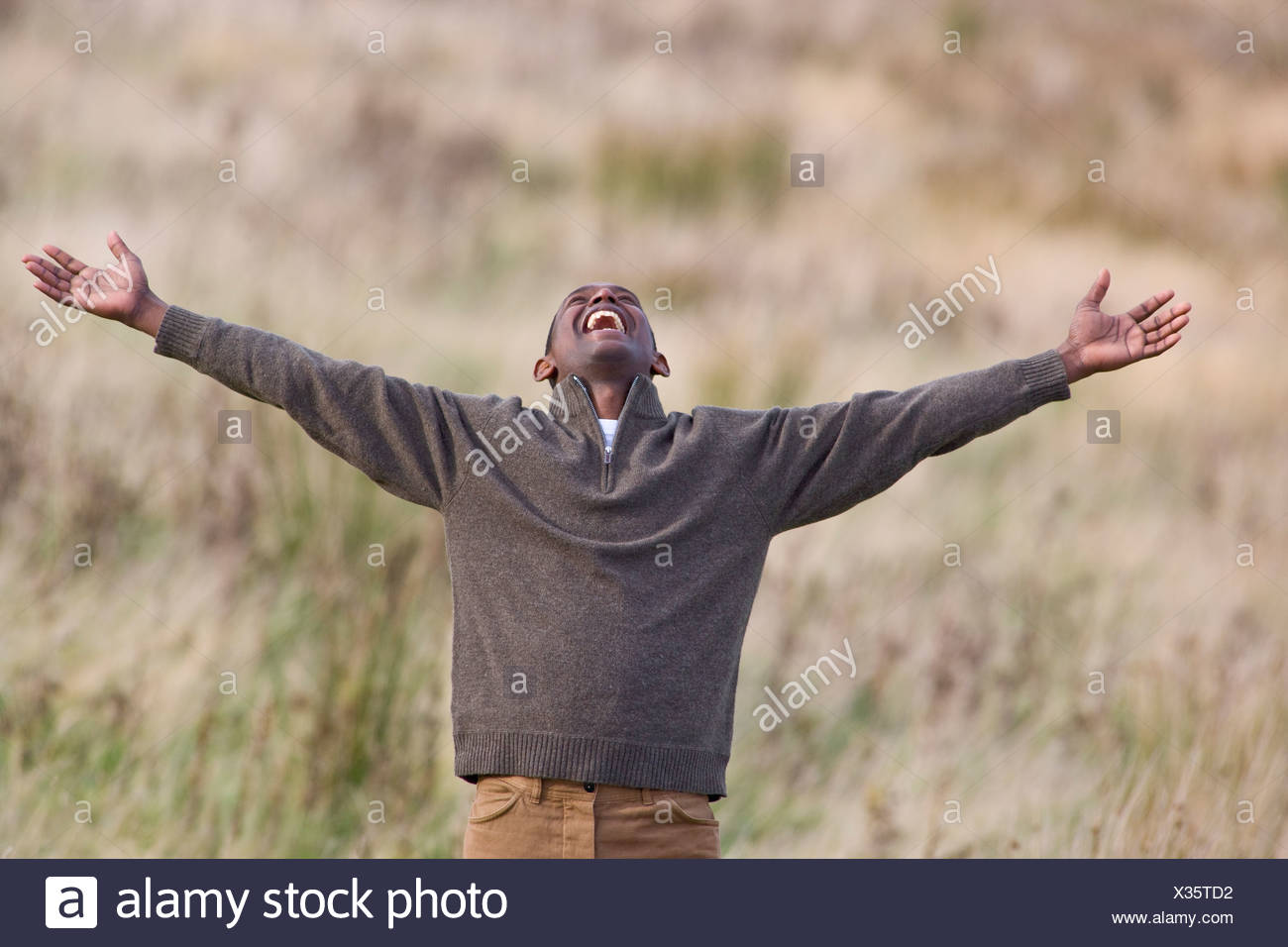 Exuberant man in field with arms outstretched - Stock Image