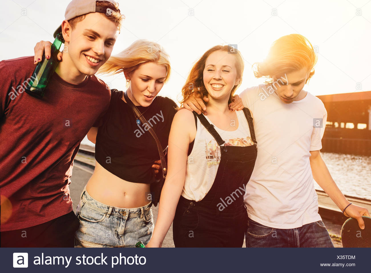 Friends walking together at the waterside - Stock Image