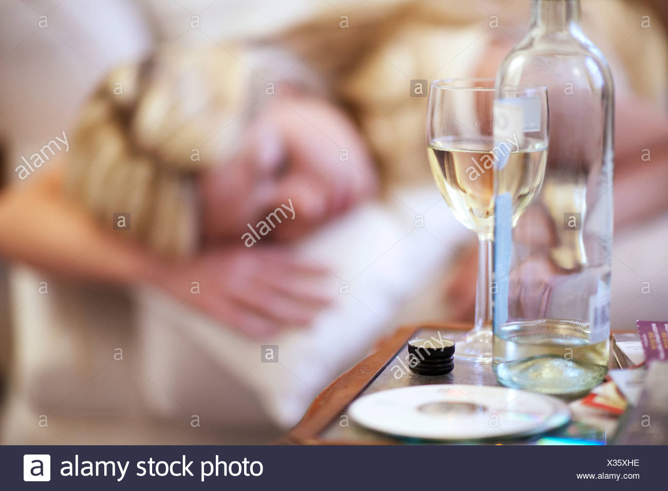 Young woman, asleep on sofa after drinking - Stock Image