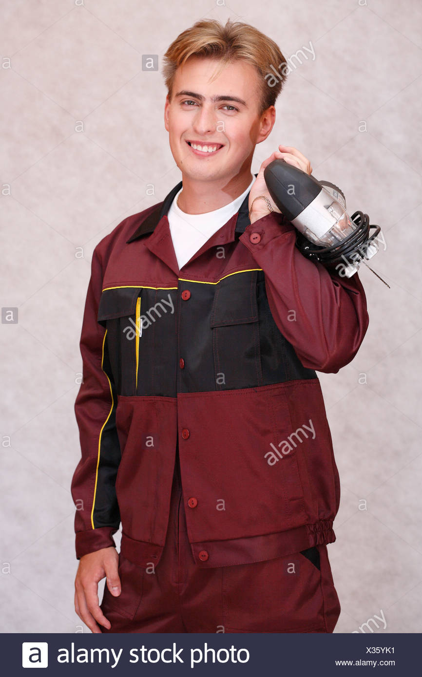 Worker Man work labour Uniform smile smiling Dress young studio portrait power tool jigsaw job occupatio - Stock Image