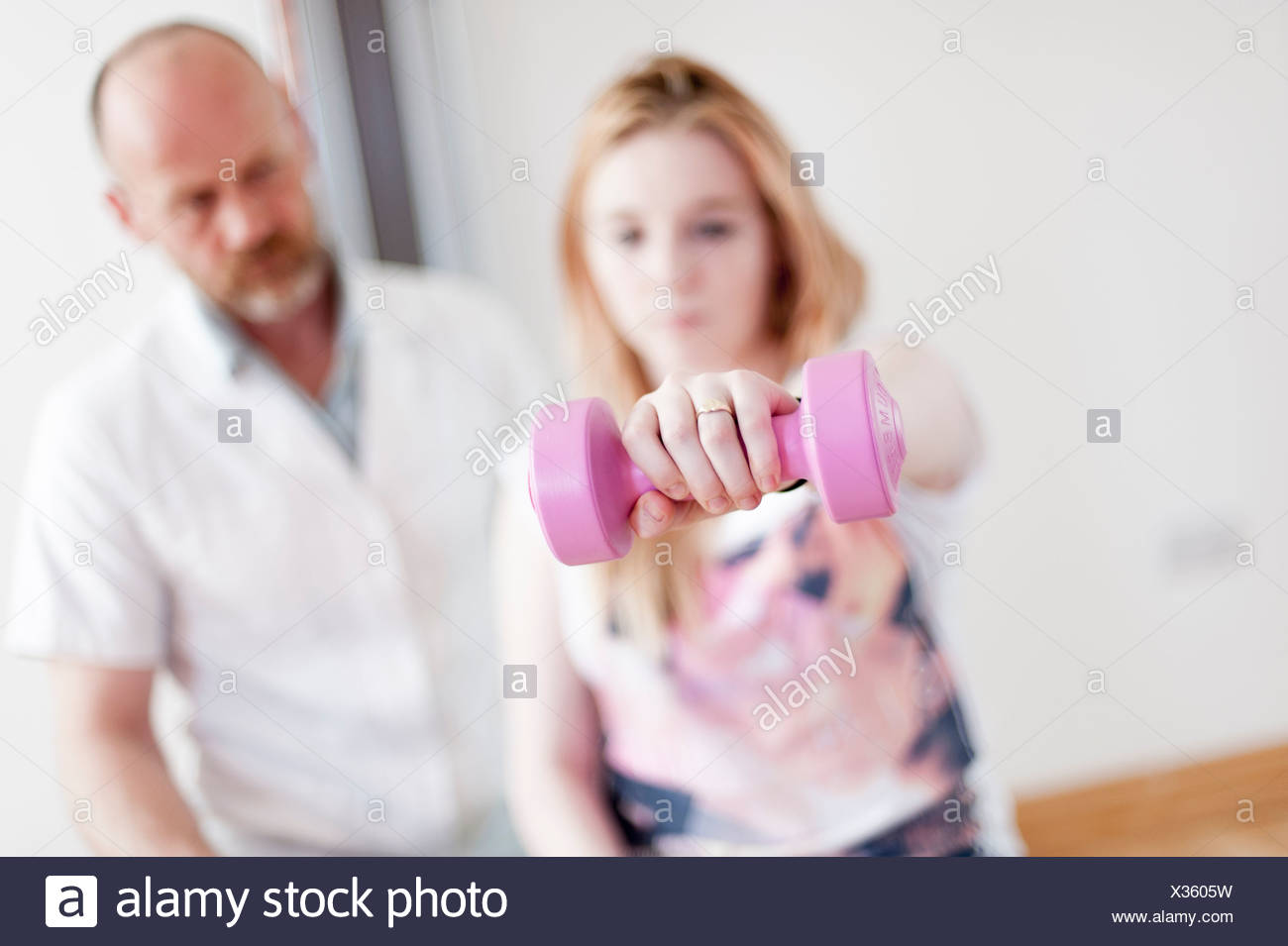 Young woman exercising with dumb bells, guided by mature man - Stock Image