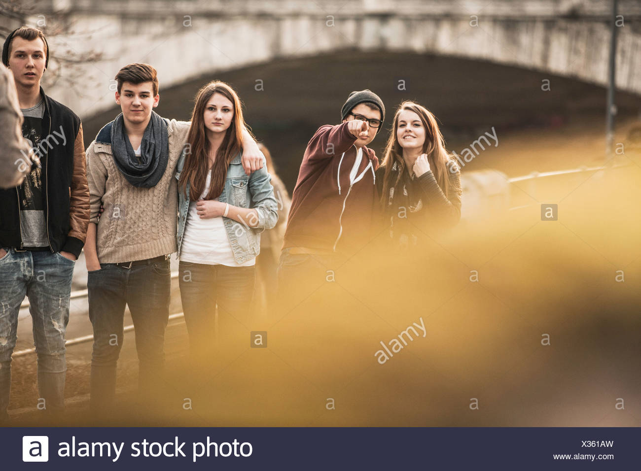 Five teenagers outdoors, boy pointing at camera - Stock Image