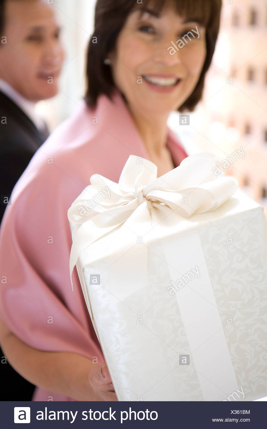 Senior couple, in formalwear, standing in hallway, woman carrying wedding gift, smiling, close-up, portrait - Stock Image