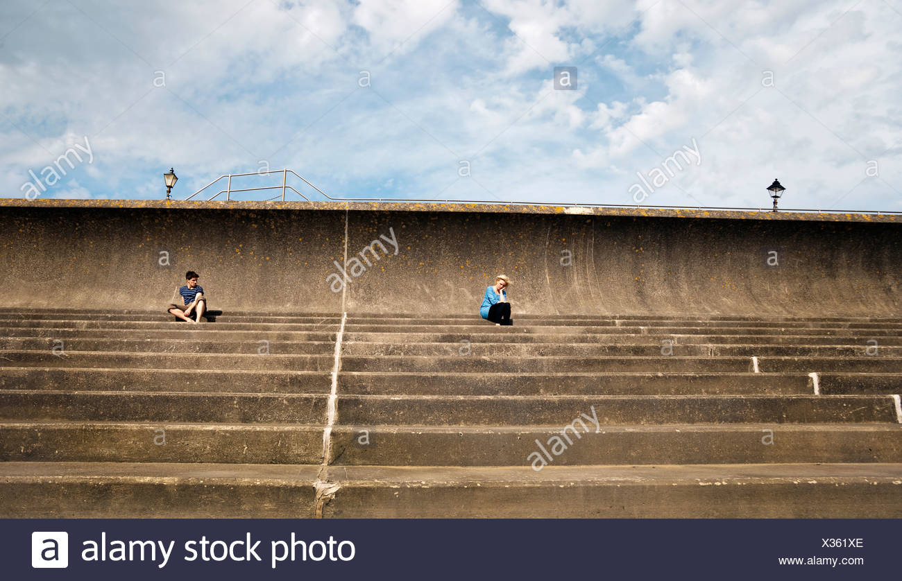 Man and woman sitting apart on steps - Stock Image