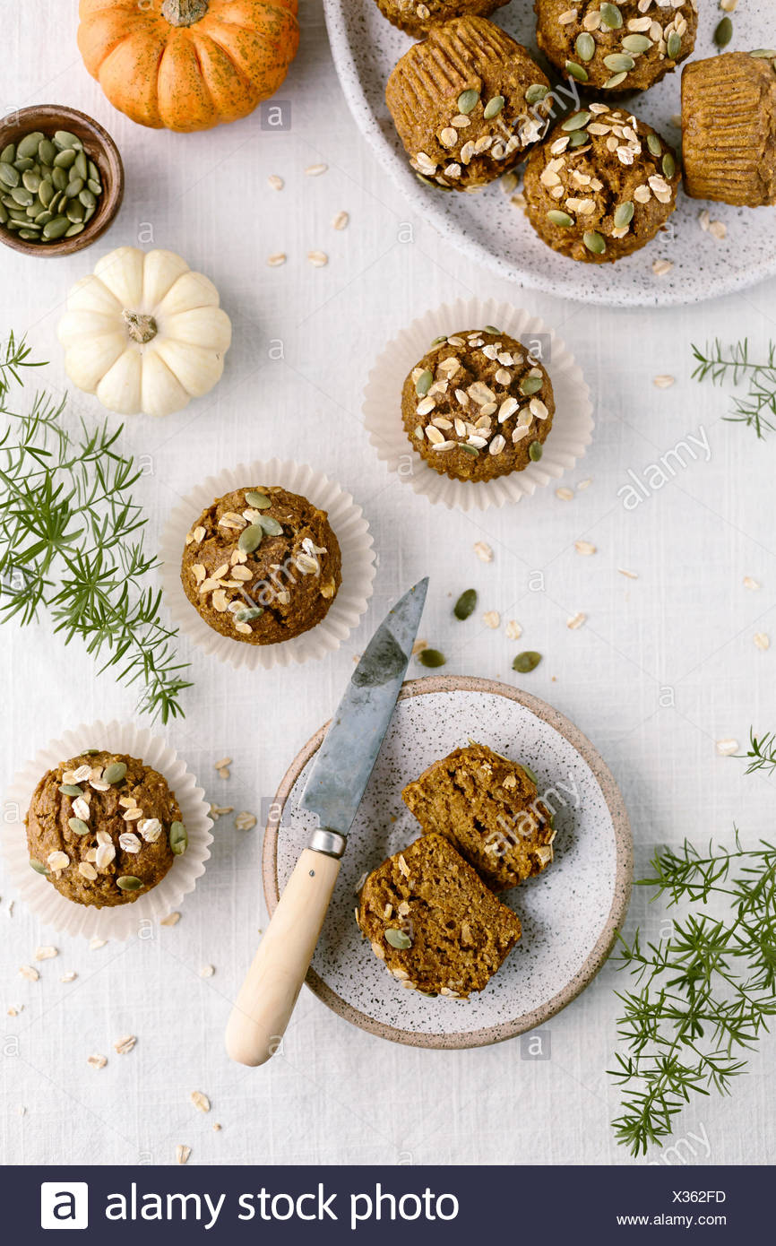 Freshly baked Maple-Sweetened Pumpkin Oat Muffins are photographed from the top view. - Stock Image