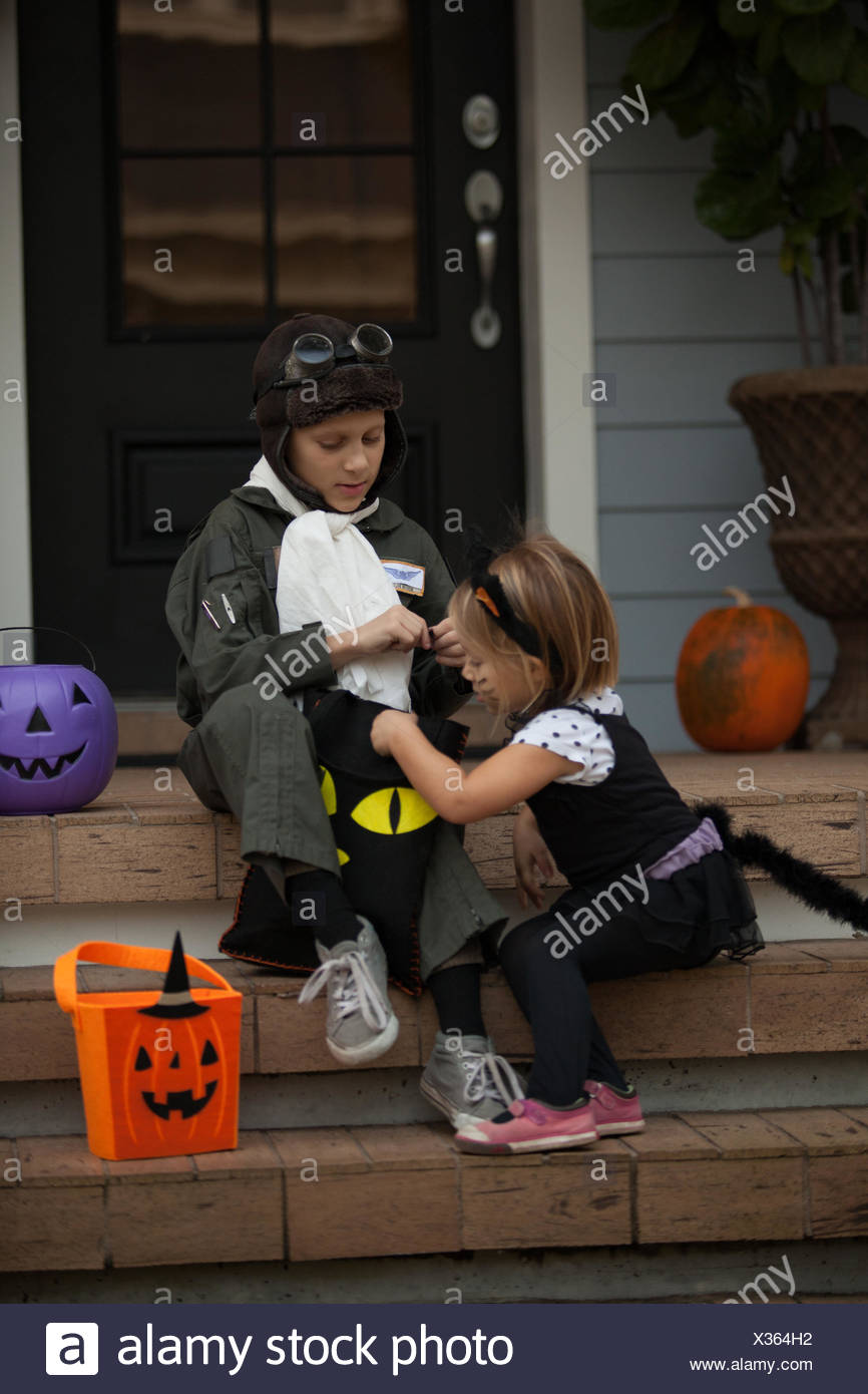 Boy and sister trick or treating in cat and pilot costume sitting on stairway looking in bags  sc 1 st  Alamy & Boy and sister trick or treating in cat and pilot costume sitting on ...