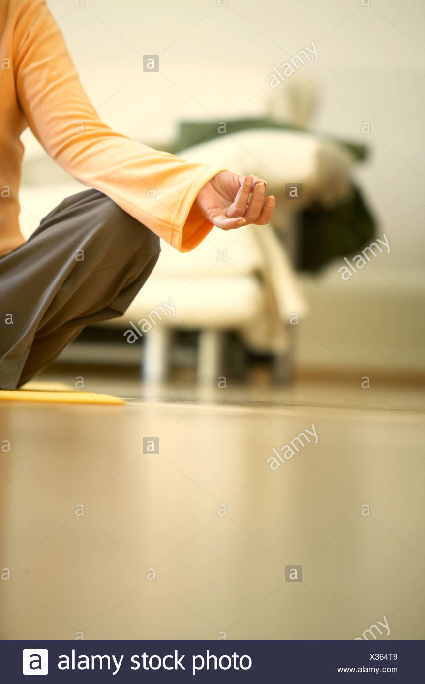 A woman sitting on a yoga mat, close-up of hand - Stock Image